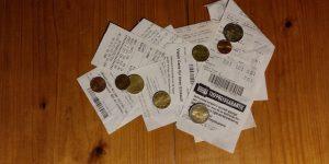 mehrere Kassenbons und Kleingeld auf einem Haufen